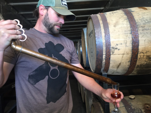 Davin pours Real spirits whiskey into glass using his handmade whiskey thief tool